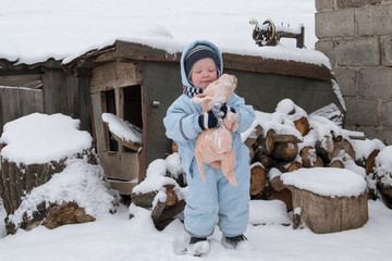 happy child in winter fashion clothes posing with a toy pig in the courtyard of his village house. First snow, family, tradition, holiday. New Year 2019 Yellow Pigs