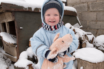 A happy child in winter fashion clothes posing with a toy pig in the courtyard of his village house. First snow, family, tradition, holiday. New Year 2019 Yellow Pigs