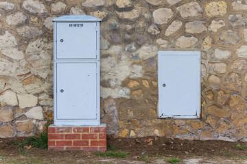 Cajas eléctricas junto a un muro de piedra