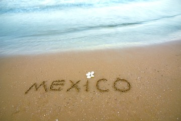 Mexico written on the sand on the beach