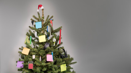 Christmas tree with decorations of business accessories and blank colored post-it notes with copy space in front of a light gray background, copy space, nobody