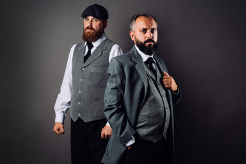 Two bearded men in strict suits standing one near one and looking on camera on black