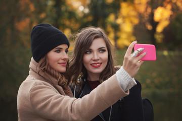 Happy best girlfriends making selfie on smartphone in autumn park outdoors