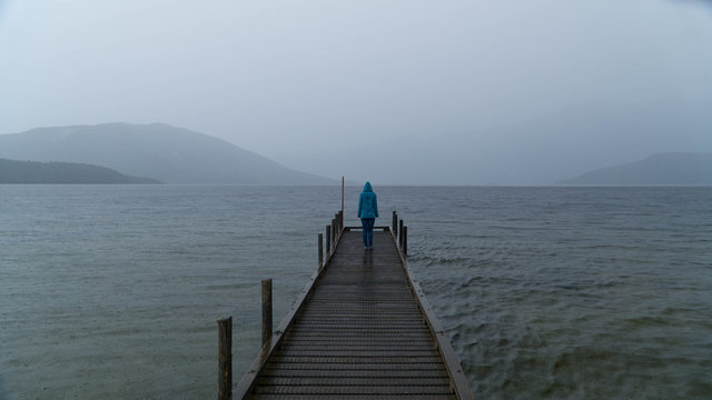 Young girl standing in the end of wooden pier, during rain in front of lake Hauroko, New Zealand