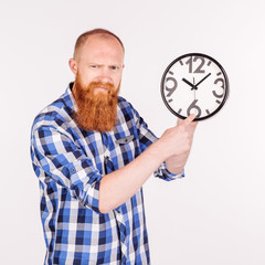bearded man holding and pointing at clock over white background