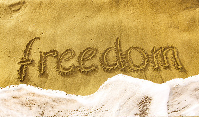inscription FREEDOM on the yellow sand