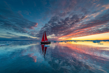 Greenland midnight Sunrise mirror panorama with red sail ship Wall mural