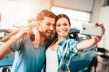 A Man And A Woman Do Selfie Near Their New Car.
