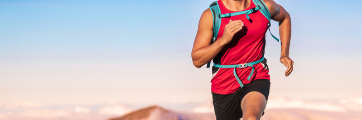 Athlete runner man running fast with backpack outdoors on blue sunset sky background with copy space. Banner panorama. Crop of midsection body, torso and arms.