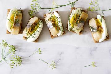 Tradition Danish open sandwich smorrebrod with herring, egg, mustard and dill. Dark bread sandwich.