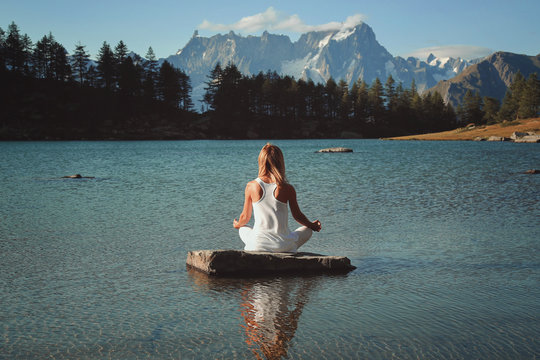 Woman meditation in mountain lake