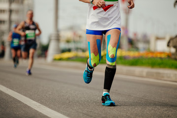 Fototapete - legs woman runner in compression socks and kinesio tape on knees