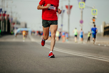 Fototapete - man runner athlete in red t-shirt and black shorts running marathon