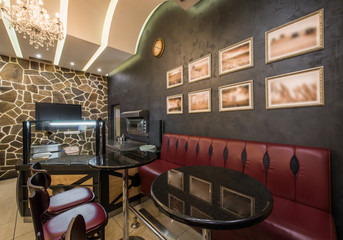 Contemporary decorated interior of pizza restaurant with shelves and seats