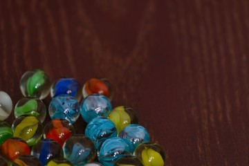 glass Marbles on dark wooden floor