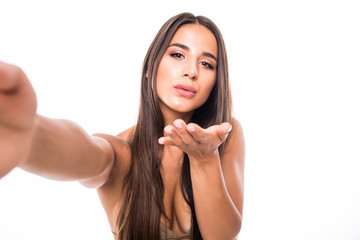 Self portrait of nice, amazing, pretty, positive, sexy woman shooting selfie in two hands on front camera, blowing air kiss to her boyfriend in bikini, isolated on white background