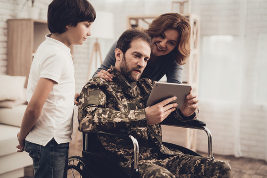 Disabled Man Soldier Watch A Tablet With Family.