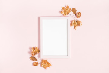 Autumn composition. Golden leaves, photo frame on pastel pink background. Autumn, fall concept. Flat lay, top view, copy space