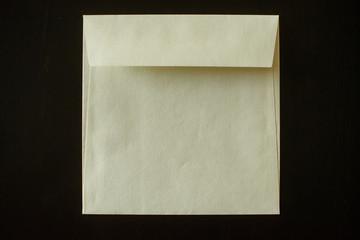 letter envelope on black background. mock-up for your design. flat lay.