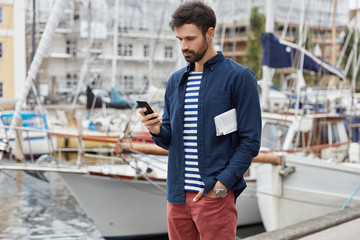 View of handsome serious bearded young guy walks along sea bay, dressed in trendy clothes, stands on seashore, waits for call on smart phone, surfes internet. Vintage effect. Street style conept