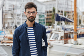 Outdoor shot of bearded young sailor dressed in fashionable clothes, has rest after arrival, poses against sailboats blurred background, carries newspaper under arm, breathes fresh marine air