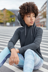 People, ethnicity, style, spare time concept. Vertical shot of fashionable woman basketball player dressed in oversized sweatshirt with hood, leggings, sits on asphalt of local court, tired after game