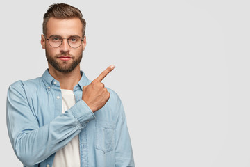 Studio shot of attractive bearded man with thick beard and stylish haircut, points with fore finger at upper right corner, shows blank space for your advertising content or promotion. Look there!