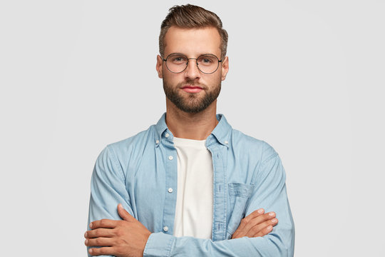 Horizontal shot of handsome self confident businessman or designer, stands crossed hands against white background, wears casual shirt, poses against white background. People and lifestyle concept