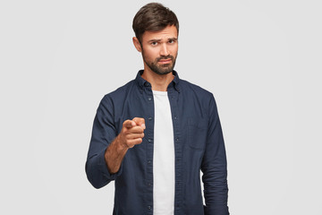 Its you who are guilty. Annoyed indignant bearded young Caucasian man points at camera with index finger, blames somebody, wears casual clothes, stands against white background. Blame concept