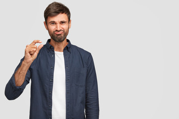 Waist up portrait of attractive young hipster with bristle shows something very little with both hands, dressed in casual clothes, isolated over white wall with copy space for your advertisement