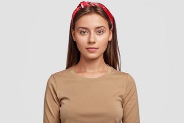 Portrait of pleasant looking European brunette girl wears stylish red headband, beige sweater, looks confidently directly in camera, listens attentively interlocutor, poses indoor. Style concept