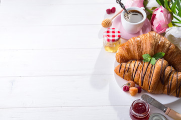 breakfast freshly baked croissant decorated with jam and chocolate, flowers on wooden table in a kitchen with copy space