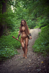 young Amazonian girl walks through a deciduous forest.