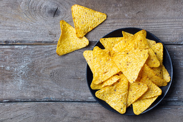 Nachos, corn chips on black plate. Wooden background. Top view. Copy space.