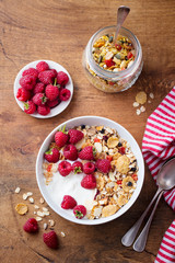 Healthy breakfast. Fresh granola, muesli with yogurt and berries on wooden background. Top view.