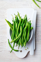 Green beans in white bowl on cutting board. Top view. Copy space.
