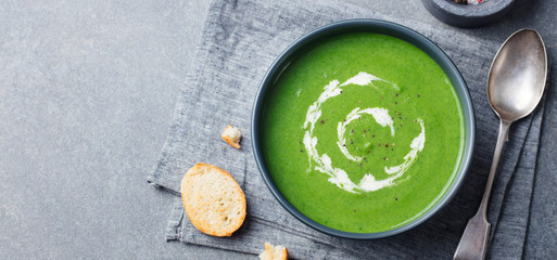 Broccoli, spinach cream soup in a bowl with toasted bread. Top view. Copy space.
