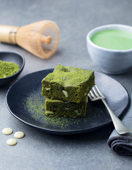 Matcha green tea cake, bars, brownie with white chocolate on a plate. Grey stone background.