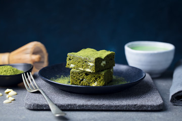 Matcha green tea cake, bars, brownie with white chocolate on a plate. Grey background. Copy space.