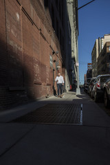 Man checking cell phone while walking dog on street in the DUMBO neighborhood of Brooklyn, New York City