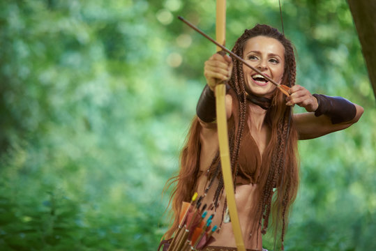 Hunting girl Amazon shoots from a wooden bow in the forest