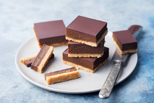 Chocolate caramel slices, bars, millionaires shortbread on a grey plate. Blue background. Close up.
