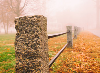 Foggy Morning of the town green stone post, iron rail fence in Ellington, CT