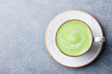 Matcha, green tea latte in a cup. Grey stone background. Top view. Copy space.