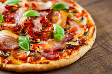 Pizza with Mozzarella cheese, mushrooms, bacon, Tomatoes, pepper, Spices and Fresh Basil. Italian pizza on wooden background.