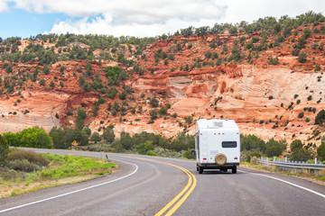 White Colour Motorhome Car Goes On Road with Background Of Mountains