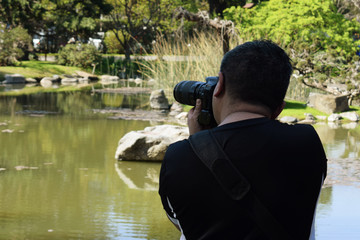 photographer takes pictures of nature near the river in summer in the park