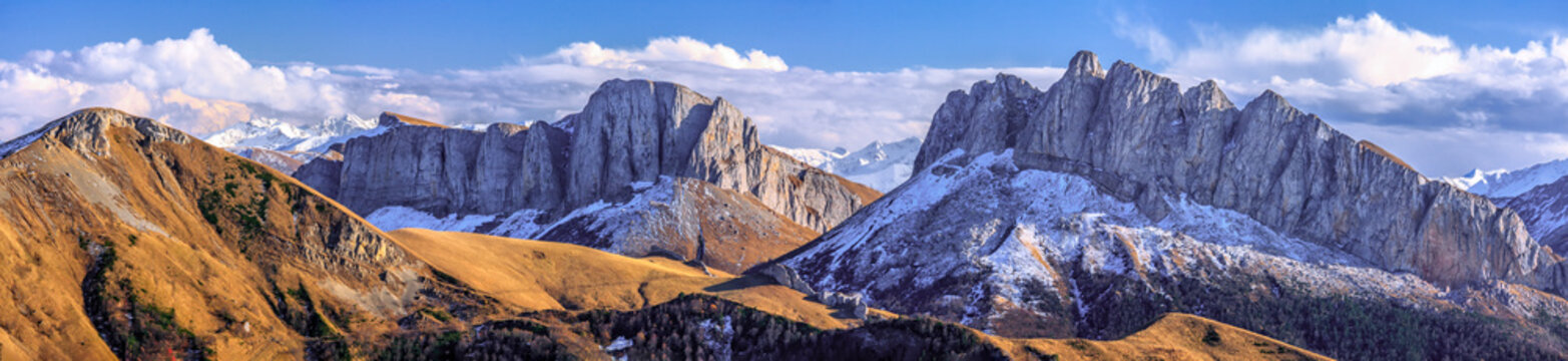 Beautiful scenic autumn landscape of majestic Acheshbok rocky mountain peaks called Devil's Gate covered with snow under blue sky with clouds. Wide panoramic mountain scenery in West Caucasus, Russia