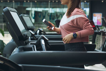 Side crop view of attractive sport woman on running track. Girl running in machine treadmill at fitness gym doing cardio. Using jogging track for heath. Concept of healthy lifestyle.