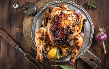 Grilled whole chicken with garlic, lemon and sage on plate on wooden table , top view